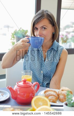 Cheerful woman having a continental breakfast in hotel
