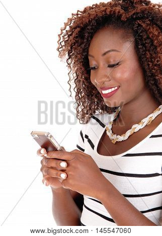 A beautiful African American woman with brunette hair standing with her cell phone and texting isolated for white background.