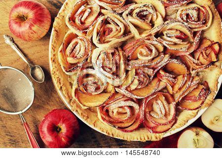 Apple pie with roses on wooden background