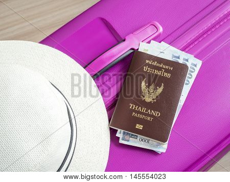 Closeup Thailand passport Taiwan banknote and white hat on pink suitcase