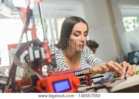 Smart female engineer is preparing 3d printer for prototyping. She is touching material with concentration