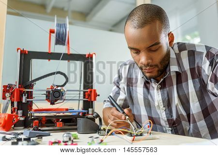 Smart young man is engineering 3d printer. He is sitting and using solder tool poster