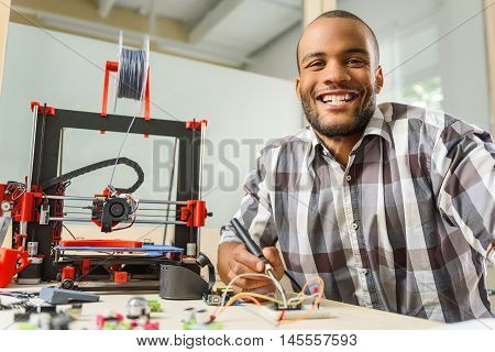 Happy male technician is working with 3d printer details. He is holding tester and smiling