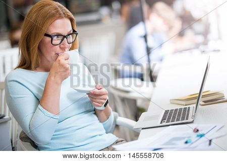 Have a break. Pleasant senor delighted woman sitting at the table and using laptop while drinking coffee