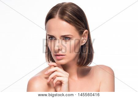 Pure skin. Wistful young woman touching her face portrait on isolated white background