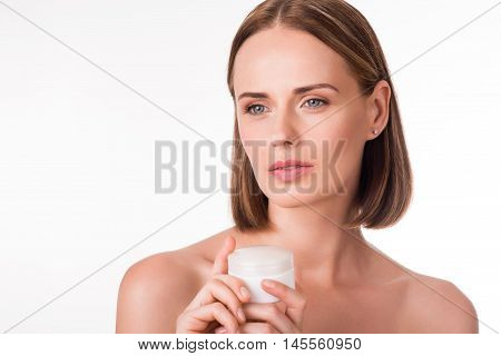 Skincare. Young adult thoughtful woman holding lotion jar being on isolated white background