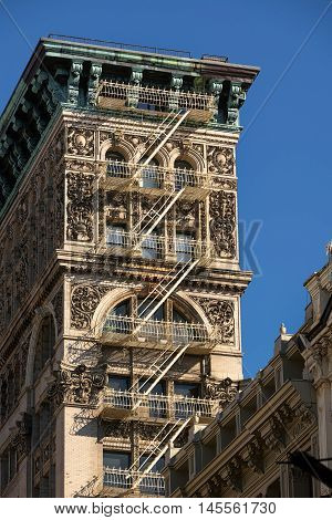 Soho building with intricate facade, terra cotta ornamentation, copper cornice and painted iron fire escape. Manhattan, New York City