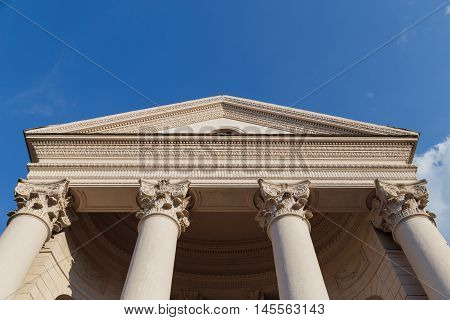 Capitol classical facade with columns on blue sky background. Bottom view