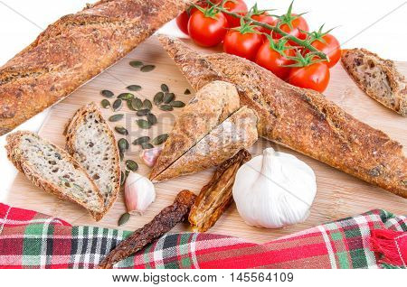 Fresh home baked Alpine Baguettes made with different cereals and seeds heart shaped slices of baguette fresh and dry tomatoes garlic and pumpkin seeds on wooden cutting board. Healthy food concept. Close-up. Top view. Horizontal.