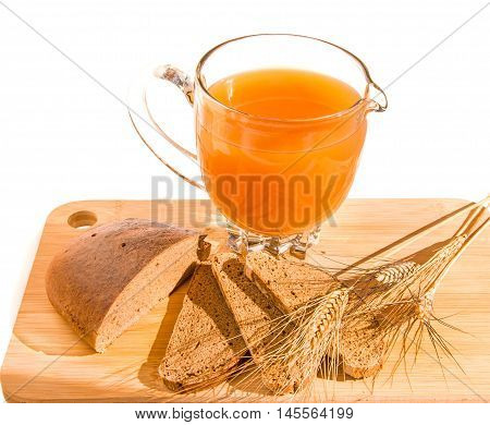 Wooden cutting board with jug of homemade traditional russian grain drink - kvass (kvas) black rye bread and ears isolated over white. Healthy food concept.