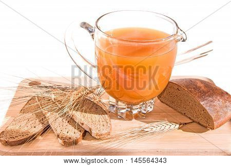 Jug with homemade traditional russian grain drink - kvass (kvas) black rye bread and ears on wooden cutting board. Healthy food concept. Horizontal.