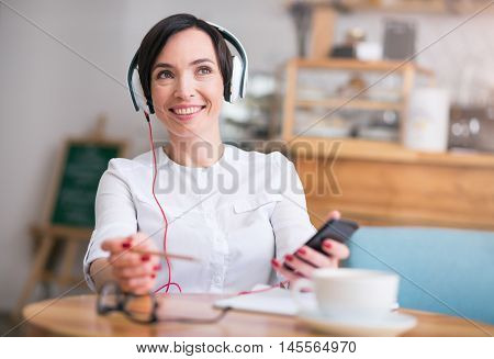 Musical break. Portrait of happy and merry woman listening music using headphones and phone while being in cafe