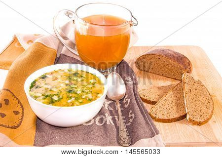 Traditional russian summer cold kvass soup okroshka with chopped potatoes eggs fresh cucumber radish green onion and sausage with greens in a white ceramic bowl jug with kvass (kvas) and black rye bread on wooden cutting board. Healthy food concept. White