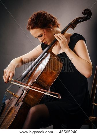 Photo of a beautiful woman concentrating on her cello playing.