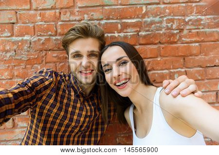 Cheerful young friends are making selfie and embracing. They are standing and stretching arms sideways. Man and woman are smiling with happiness