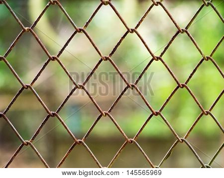 Rust steel metal net for security fence with blur nature green in background.