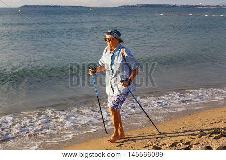 GRODNO BELARUS - SEP 02: An elderly woman practicing Nordic walking in Nesebar Bulgaria at September 02 2016