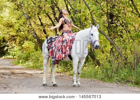 Young woman dressed in colourful dress decorated with playing cards  sits on horseback with arms stretched to sides and face to sky in park.