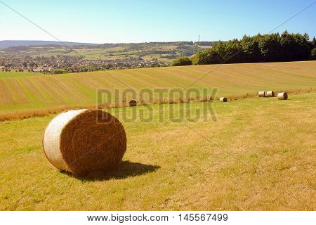 View on the coils of hay and agricultural fields and the town Bad Pyrmont in Germany.
