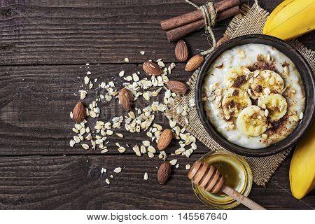 organic oatmeal porridge in dark ceramic bowl with banana, cinnamon, honey and almonds. healthy breakfast. top view