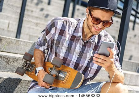 Carefree young man is listening to music from earphones. He is holding mobile phone and laughing. Guy is sitting on stairs and holding skateboard poster
