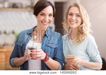 Friendly. Cheerful and delighted women eating sweet deserts and holding smart phone being in cafe and hanging out together