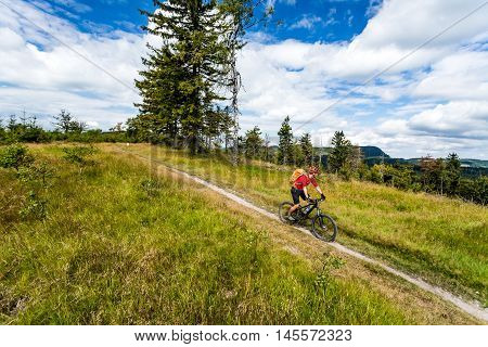 Mountain biking man riding on bike in summer inspirational mountains landscape. Rider cycling MTB on enduro trail path. Sport fitness motivation and inspiration. Rider mountain biker in summer woods.