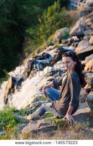 scenic view, girl sitting on rocks near a waterfall