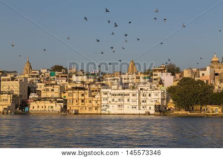 UDAIPUR INDIA - 20TH MARCH 2016: A view of part of the City of Udaipur at the lake waterfront during the day close to sunset. People birds and boats can be seen.