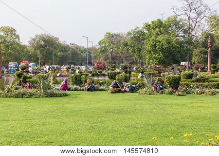 DELHI INDIA - 19TH MARCH 2016: Gardeners maintaining the gardens near the Canopy located near India Gate in Delhi during the day.
