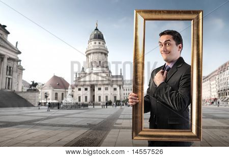 Smiling man holding a frame with monument on the background
