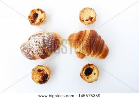 Top view of four Portuguese Nata pastries and two Portuguese croissants on white background.