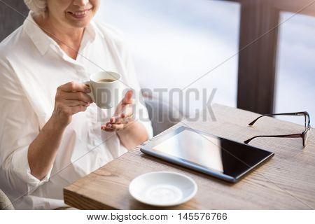 Enjoy the taste. Positive delighted senor woman smiling and drinking coffee while sitting at the table