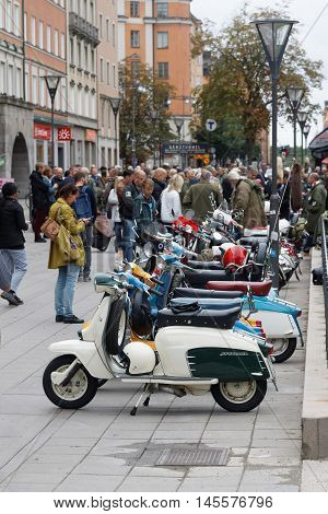 STOCKHOLM SWEDEN - SEPTEMBER 03 2016: People admiring the parked retro vespa scooters before the start of the Mods vs Rockers event at the Saint Eriks bridge Stockholm Sweden September 03 2016