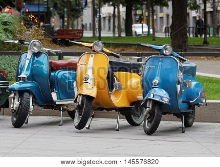 STOCKHOLM SWEDEN - SEPT 03 2016: Three beautiful blue and yellow retro vespas parked before the start of the Mods vs Rockers event at the Sanit Eriks bridge Stockholm Sweden September 02 2016