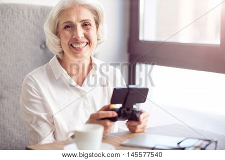 Express positivity. Cheerful content senior woman smiling and holding game console while sitting at the table