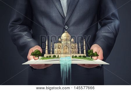 Cropped portrait of businessman holding an open book with a sketch of Taj Mahal on the top of it. World Heritage. Business travel. City of Agra. Uttar Pradesh.