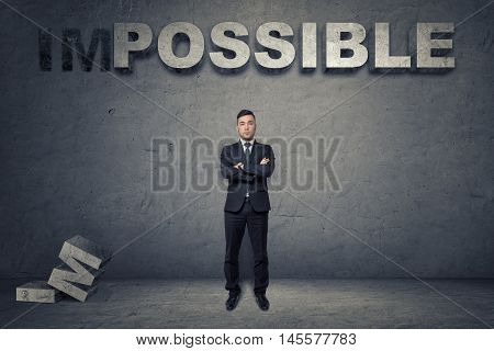 Front view of a buisnessman standing with folded arms under big 3d concrete word 'possible'. Nothing is impossible. Unlimited opportunities. Progressive ideas.