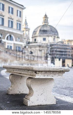 Italy, Rome, Piazza del Popolo - A bench in Piazza del Popolo with Santa Maria in Montesanto on background