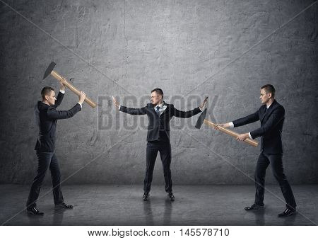 Businessman with raised hands separating two fighting businessmen with hammers. Conflicts and disputes. Collision and controversy. Pulling apart. poster