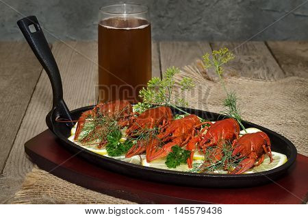 Boiled crawfish with lemon, herbs and beer. In a cast iron skillet and an old wooden background