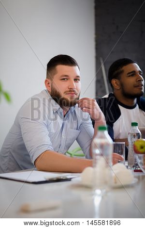Picture of handsome businessman sitting at table in board room in office. Bearded man listening to business performer and taking notes.