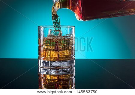 Pouring a drink. Pouring a glass of liquor from a glass bottle.