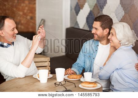 Express your emotions. Cheerful senor couple sitting at the table and talking photos with their delighted adult grandson while resting in the cafe
