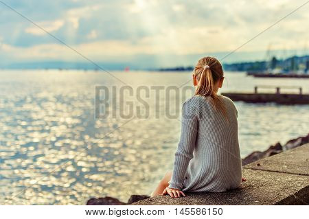 Cute little girl resting by the lake, admiring amazing sunset, rays of light falling through clouds