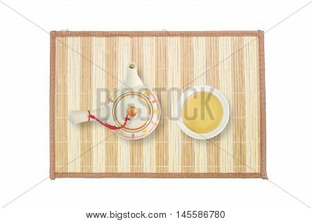 Closeup ceramic tea pot and tea cup with brown tea on wood mat isolated on white background