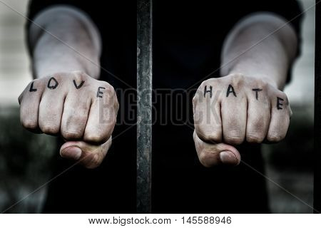 Man stretching his arms forward. Hands clenched into fists. In the hands of inscribed words