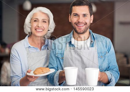 Hospitable people. Cheerful content woman and her adult grandson smiling and holding cup with tea and just baked croissants