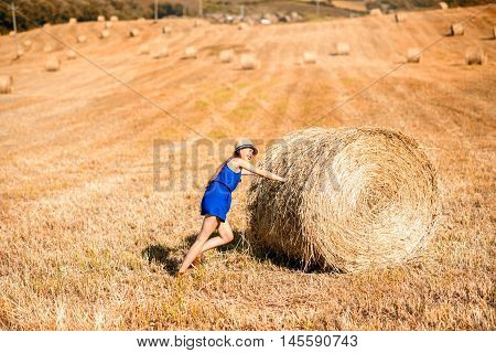 Young woman in blue dress pushing hay roll on the hayfield in Tuscany in Italy