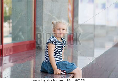 Caucasian girl 5 years old curly-haired blond sitting near the glass storefront